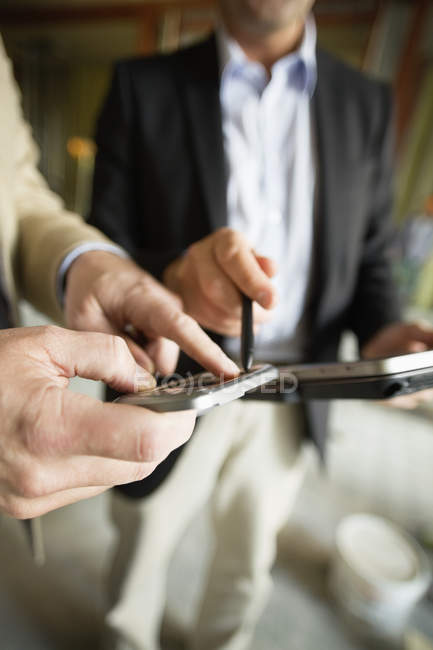 Бизнесмены, использующие смартфоны в офисе — стоковое фото