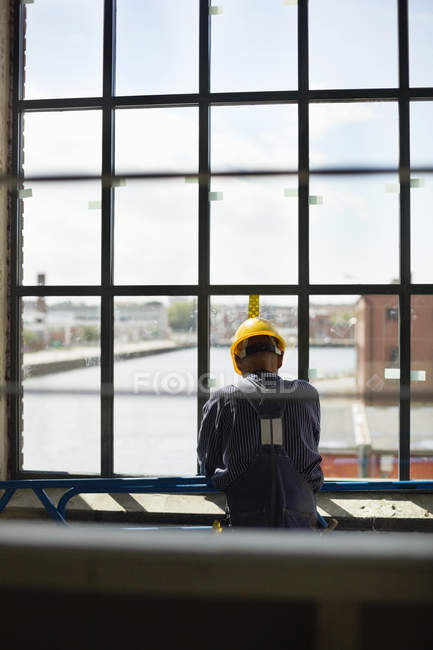 Construction worker standing by window — Stock Photo