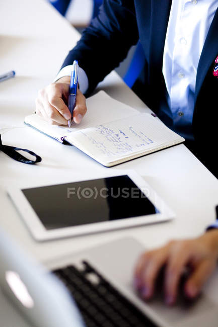 Businessman writing in diary — Stock Photo