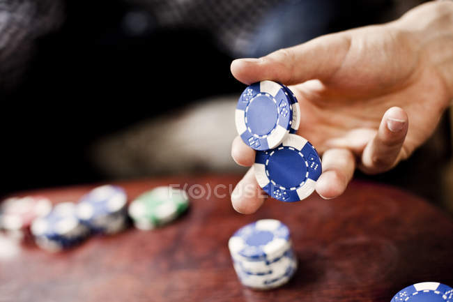 Hand holding poker chips — Stock Photo
