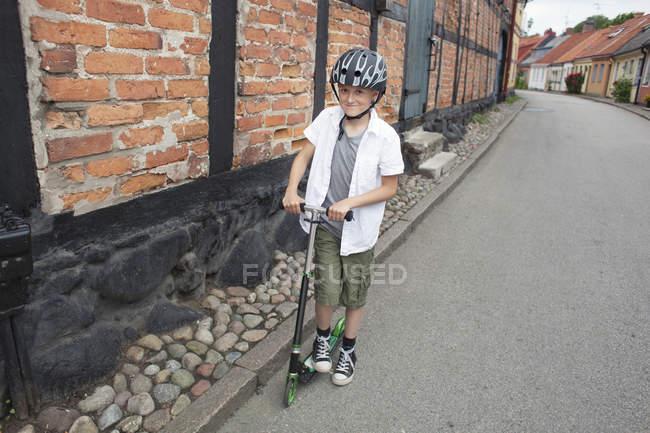 Heureux garçon équitation pousser scooter — Photo de stock