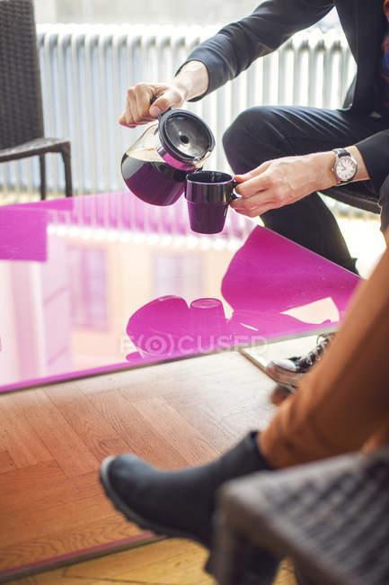 Бизнесмен разлива кофе в кружку — стоковое фото