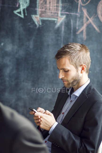 Homem de negócios usando telefone inteligente — Fotografia de Stock