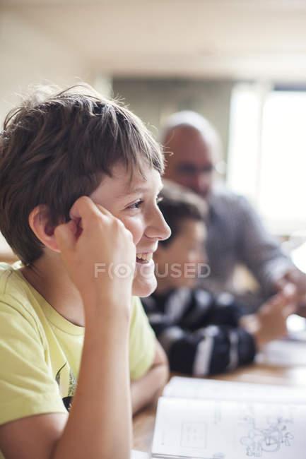 Щасливі хлопчик, сидячи в класі — стокове фото