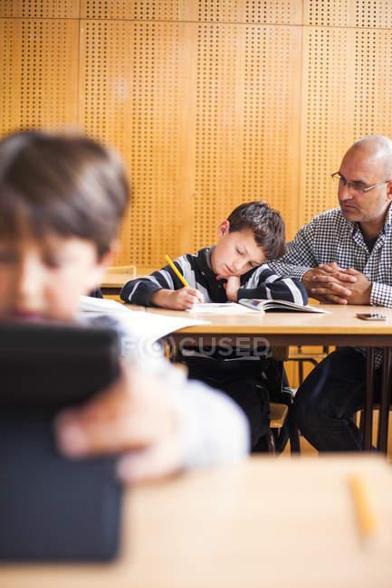 Écolier aide enseignant au comptoir — Photo de stock