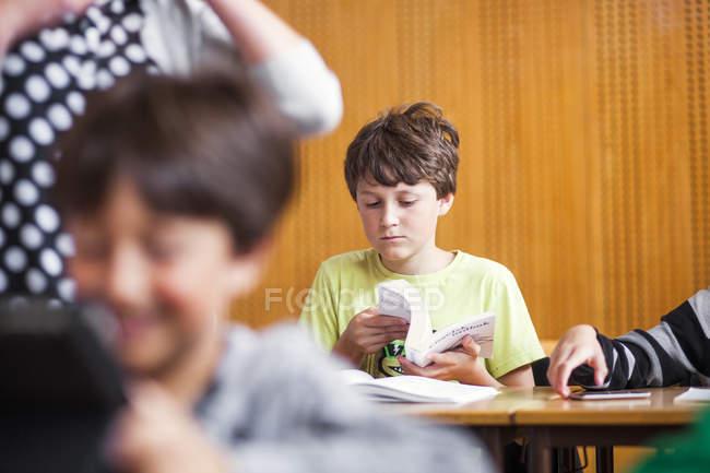 Junge Lesebuch im Klassenzimmer — Stockfoto