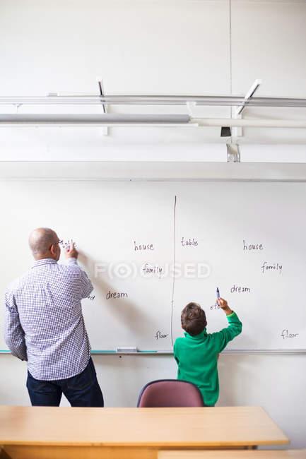 Profesor y alumno escribiendo en pizarra - foto de stock