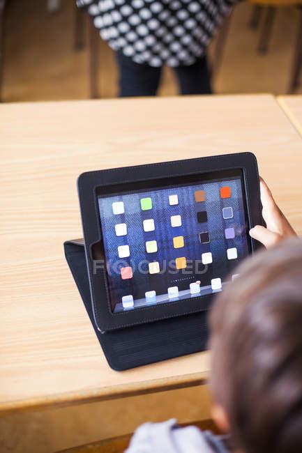 Schoolboy using digital tablet — Stock Photo