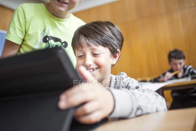 Rapaz feliz usando tablet digital — Fotografia de Stock