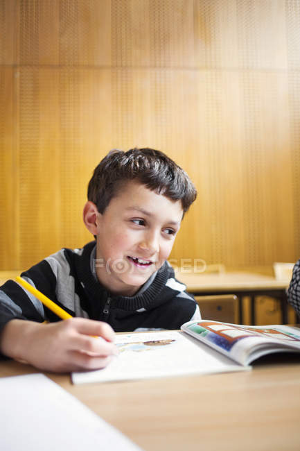 Ragazzo felice scrivendo alla scrivania — Foto stock