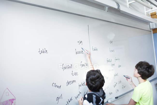 Écoliers écrivant orthographes — Photo de stock