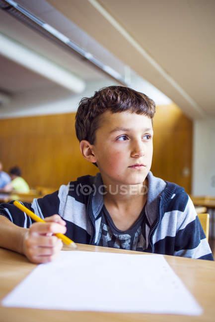 Scolaro pensieroso seduto alla scrivania — Foto stock