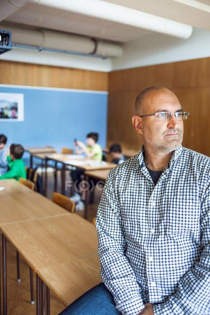 Insegnante premuroso che si siede sulla scrivania — Foto stock