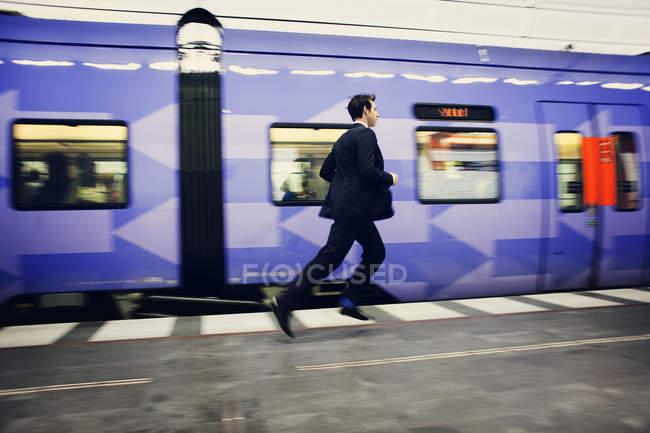 Businessman running on platform — Stock Photo