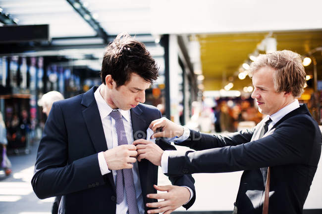 Businessman adjusting colleagues pocket — Stock Photo