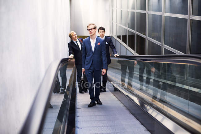 Business colleagues standing on escalator — Stock Photo