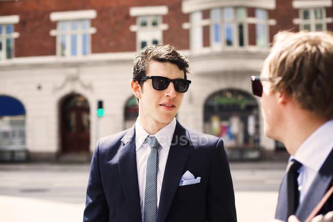 Uomini d'affari ne mentre levandosi in piedi sulla strada — Foto stock