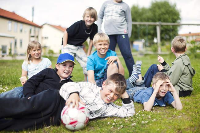 Счастливые школьники с футбольными мячами — стоковое фото