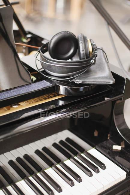 Наушники на фортепиано в студии — стоковое фото