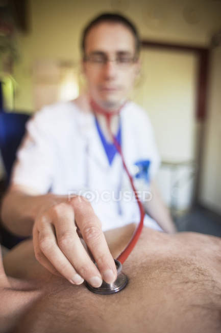 Doctor positioning stethoscope on male patient — Stock Photo