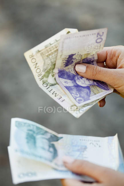 Woman holding Danish paper currency — Stock Photo