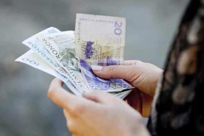 Woman holding Danish banknotes — Stock Photo