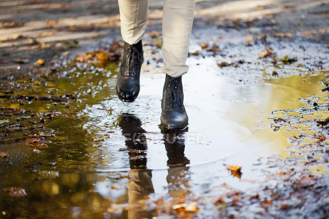 Woman walking on puddle — Stock Photo