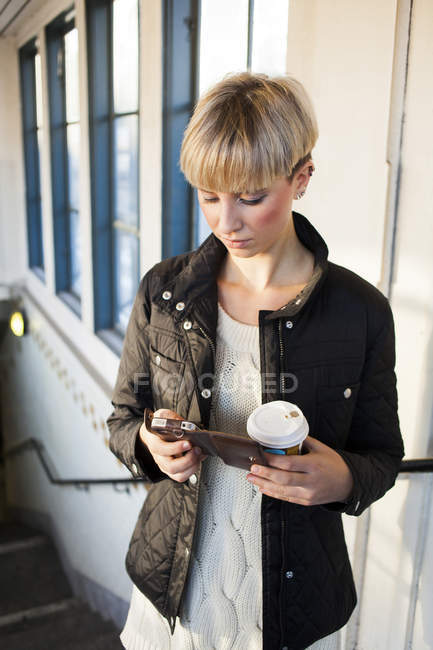 Woman with coffee cup using mobile — Stock Photo