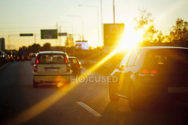 Voitures dans la rue pendant le coucher du soleil — Photo de stock
