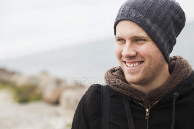 Happy man looking away at lakeshore — Stock Photo