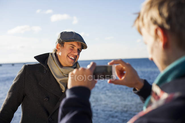 Man photographing happy gay partner — Stock Photo