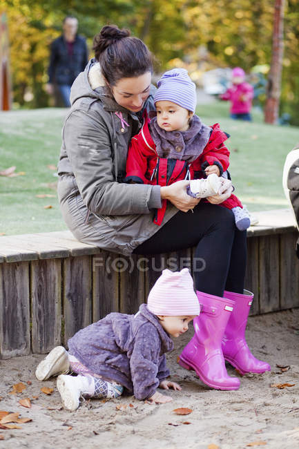 Woman sitting with daughters — Stock Photo