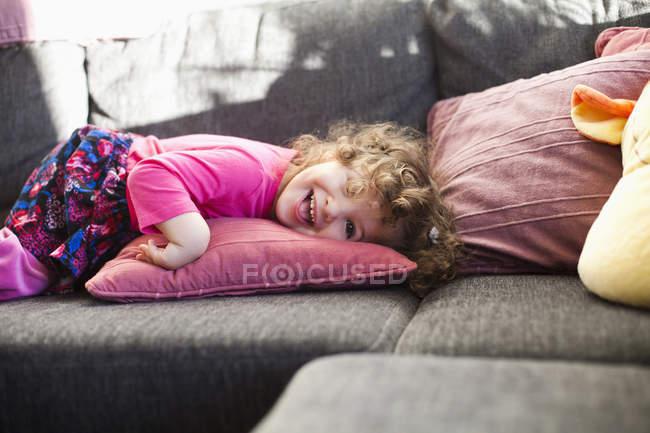 Cheerful girl lying on sofa — Stock Photo