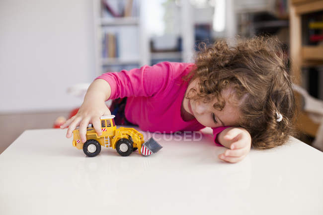 Cute girl playing with toy car — Stock Photo