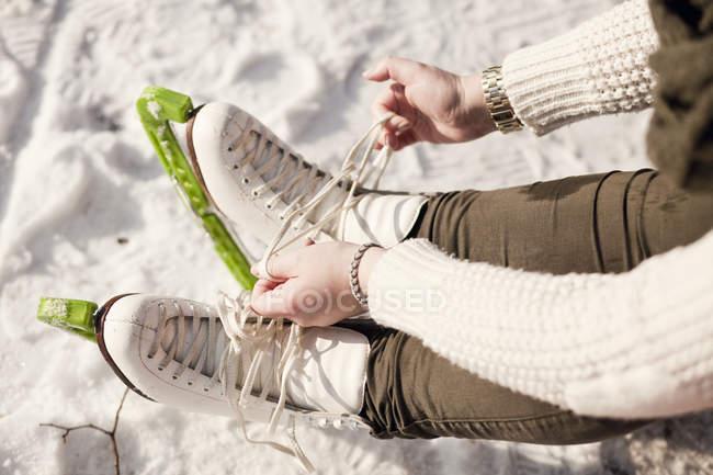 Mulher amarrando laço de patins de gelo — Fotografia de Stock