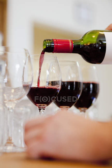 Hands pouring red wine in glass — Stock Photo