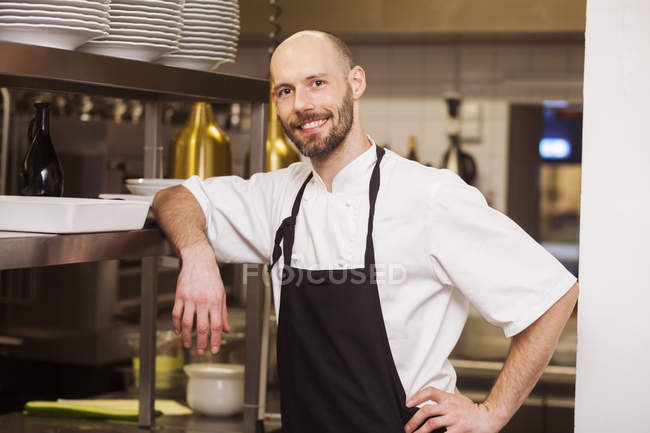 Happy chef standing at commercial kitchen — Stock Photo