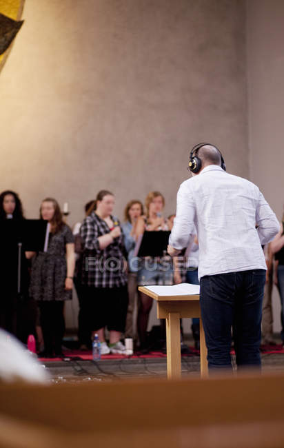 Musical conductor with choir — Stock Photo