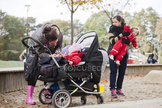 Women with daughters standing in playground — Stock Photo