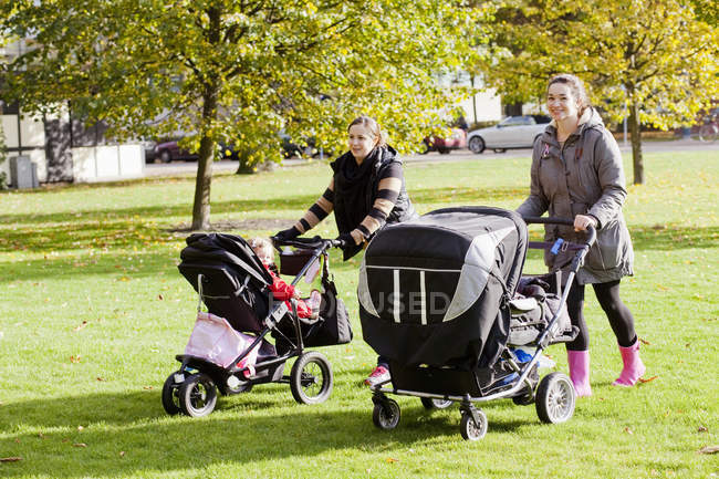 Women walking with baby carriages — Stock Photo