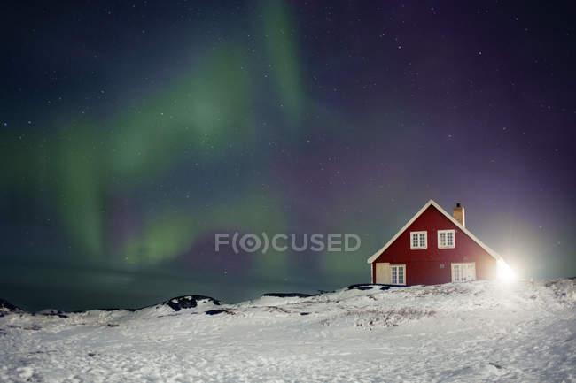 Північне сяйво над червоний будинок — стокове фото