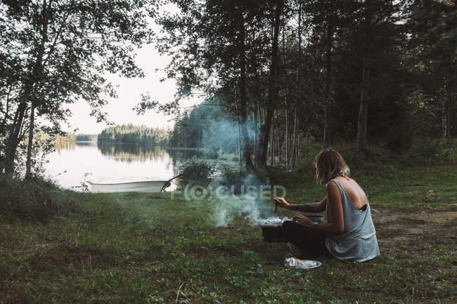 Жінка шашлики біля озера — стокове фото