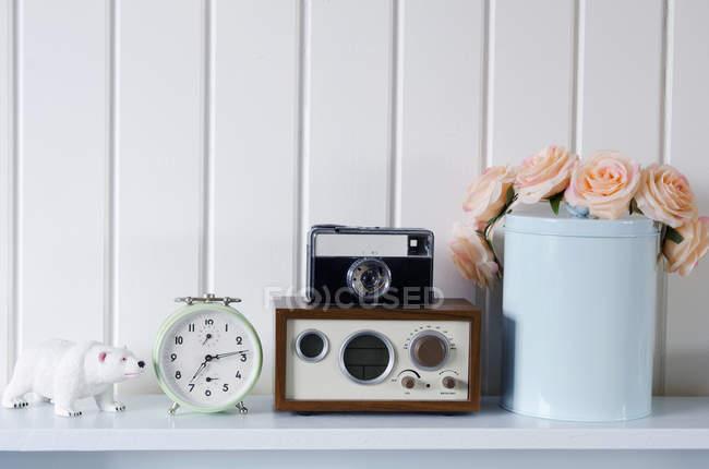 Reloj vintage y cámara en estante - foto de stock