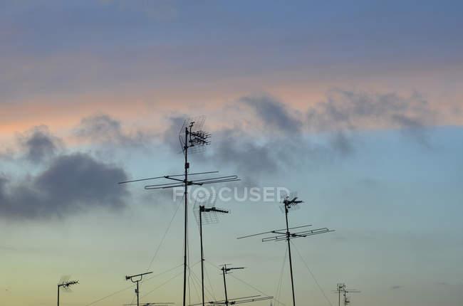 Silueta de antenas contra el cielo nublado - foto de stock