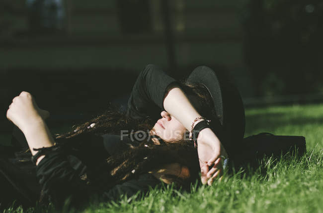 Young woman lying down in grass — Stock Photo