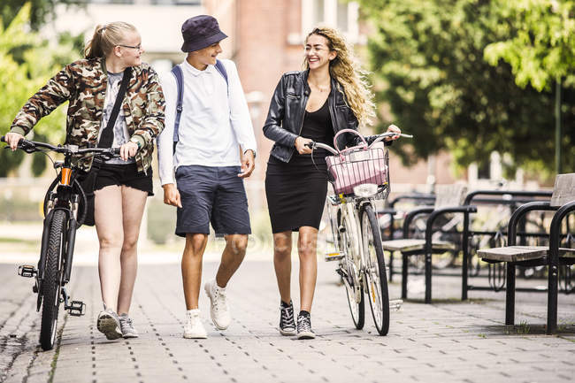 Students walking with bicycles — Stock Photo