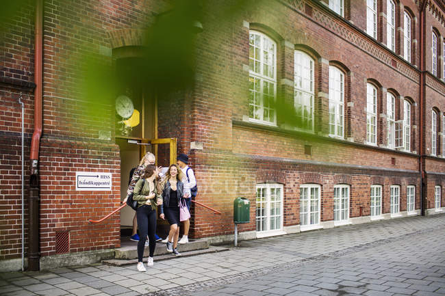 Young Students leaving school — Stock Photo