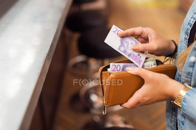 Woman paying with cash at bar — Stock Photo
