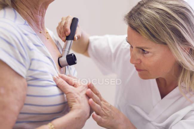 Doctor examining skin — Stock Photo