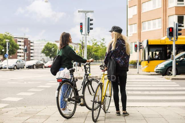 Women pushing bikes in town — Stock Photo